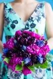 Het bruidsmeisje houdt een huwelijksboeket van tulpen en pionen in purple Royalty-vrije Stock Afbeeldingen