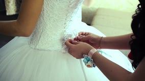Het bruidsmeisje rijgt witte huwelijkskleding voor bruid stock video