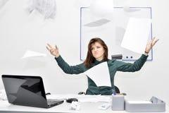 Het bruin-haired meisje in het bureau in verontwaardiging wierp op documenten en documenten stock fotografie