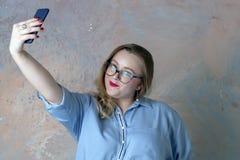 Het bruin-haired meisje maakt selfie met de telefoon stock foto's