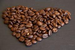 Het bruine die hart van koffiebonen op een zwarte leiplaat wordt gevormd royalty-vrije stock afbeelding