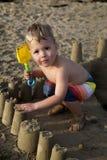 Het bruine eyed blonde jongen spelen in een zandkasteel op het strand Stock Foto's