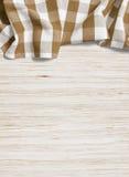 Het bruine gevouwen tafelkleed over eik bleekte houten lijst Stock Afbeeldingen