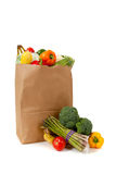 Het bruine hoogtepunt van de kruidenierswinkelzak van groenten op wit stock afbeeldingen