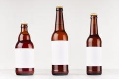Het bruine inzamelings verschillende type van bierflessen met leeg wit etiket op witte houten raad, bespot omhoog stock foto