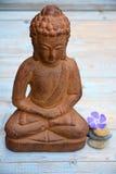Het bruine standbeeld van Boedha met bloemen en zen stenen Royalty-vrije Stock Foto's
