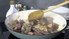 Het bruinen van kubussen van gesneden rundvleeslapje vlees in een koekepan stock videobeelden