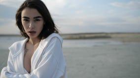 Het brunette bevindt zich op een zandige meerkust stock video