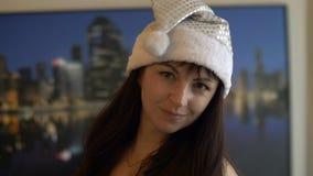 Het brunette die van portretkerstmis en aan de camera in Kerstmanhoed glimlachen kijken stock foto