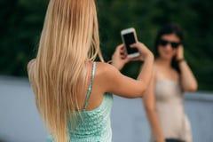 Het brunette en het blonde worden gefotografeerd en genieten van het leven Zonnige dag De zomer Royalty-vrije Stock Afbeelding