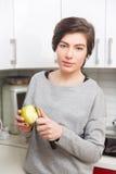 Het brunette maakt appel met mes schoon stock afbeelding