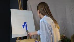 Het brunette smeert de blauwe verf op het canvas met een spatel stock videobeelden
