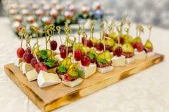 Het buffet bij de ontvangst Assortiment van canapes op houten raad De banketdienst cateringsvoedsel, snacks met kaas, jamon en royalty-vrije stock foto's