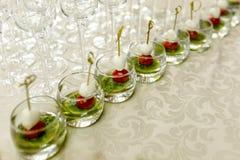 Het buffet bij de ontvangst Glazen wijn en champagne op achtergrond Assortiment van canapes in glaskoppen De banketdienst stock foto's
