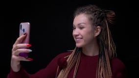 Het buitengewone donkerbruine meisje met dreadlocks maakt smilingly selfie-foto's en zijnd blij op zwarte achtergrond stock video