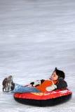 Het Buizenstelsel van de jongen onderaan SneeuwHeuvel. Royalty-vrije Stock Foto's