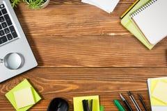 Het bureau van de bureaulijst met reeks kleurrijke levering, wit leeg notastootkussen, kop, pen, PC, verfrommelde document, bloem stock afbeelding