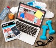 Het bureau van de houten sportman in hoge definitie met laptop, tablet en stock afbeeldingen