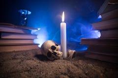 Het Bureau van de tovenaar Een bureau door kaarslicht dat wordt aangestoken Een menselijke schedel, oude boeken op zandoppervlakt Stock Afbeelding
