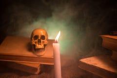 Het Bureau van de tovenaar Een bureau door kaarslicht dat wordt aangestoken Een menselijke schedel, oude boeken op zandoppervlakt Stock Fotografie