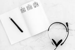 Het bureau van musicus voor songwriter het werk met hoofdtelefoons en de nota's marmeren achtergrond hoogste meningsmodel stock fotografie
