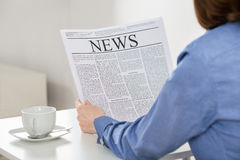 Het Bureau van onderneemsterreading newspaper in royalty-vrije stock afbeeldingen