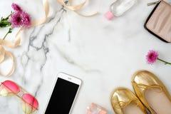 Het bureau van vrouwen met modieuze toebehoren en apparaten De mobiele telefoon, zonnebril, beurs, gouden kleurensandals, madelie royalty-vrije stock foto