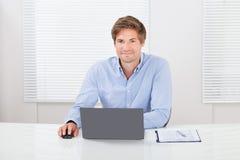 Het Bureau van zakenmanusing laptop in Stock Afbeelding