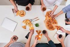 Het bureaupersoneel eet pizza en drinkt koffie in bedrijfsoffi stock fotografie