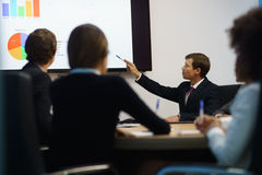 Het Bureauvergadering van managerdoing presentation at met Grafieken op TV Royalty-vrije Stock Afbeelding
