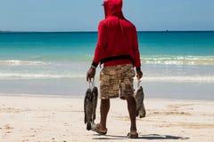 Het Cara?bische visser lopen op een strand in de Dominicaanse Republiek, die freshl vist, enkel gevangen verkopen Verbazende turk stock fotografie