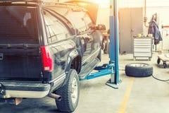 Het centrum van de autodienst Oud roestig die offroad SUV-voertuig op lift bij onderhoudspost wordt opgeheven Automobiele reparat royalty-vrije stock fotografie