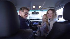 Het centrum van de autoverkoop, gelukkige familie met mooi jong geitjemeisje toont positief gebaar terwijl nieuwe auto in salon i stock video