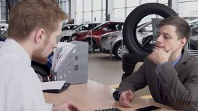 In het centrum van de handelaarsauto ontvangt de cliënt raad van specialist over voertuig Langzame Motie stock video
