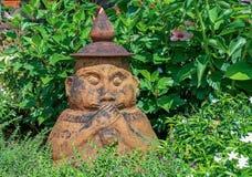 Het ceramische standbeeld van Weinig Boedha eet brood Stock Fotografie