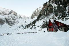 Het Chalet van de bergredding op een vallei, door bergen wordt omringd die royalty-vrije stock afbeeldingen