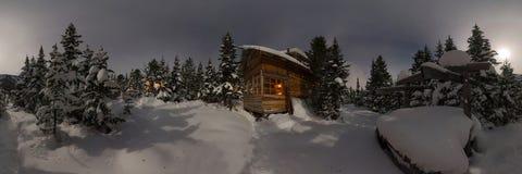 Het Chalet van het panoramahuis tijdens een sneeuwval in het bos van de bomenwinter bij nacht in het maanlicht Cilindrical 360 pa stock foto