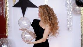 Het charismatische meisje in een zwarte kleding werpt op ballons Feestelijke atmosfeer stock videobeelden