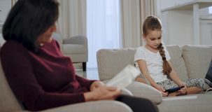 Het charismatische meisje spelen op een smartphonespel terwijl haar grootmoeder het lezen van een boek op de bank in a concentree stock video