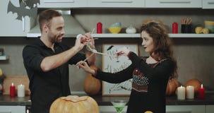 Het charismatische paar bij Halloween-nacht het spelen met een skelet, heeft samen een grappige tijd stock videobeelden