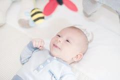 Het charmante baby spelen met een stuk speelgoed die op rug liggen Royalty-vrije Stock Foto