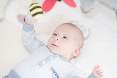 Het charmante baby spelen met een stuk speelgoed die op rug liggen Stock Afbeeldingen