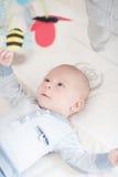Het charmante baby spelen met een stuk speelgoed die op rug liggen Stock Foto