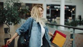 Het charmante blondemeisje in jeansjasje wervelt met het winkelen zakken in de wandelgalerij stock footage