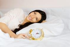 Het charmante donkerbruine meisje liggen op bed met gouden Royalty-vrije Stock Foto's