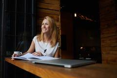 Het charmante gelukkige vrouw genieten van rust en goede dag terwijl het zitten alleen in het moderne binnenland van de koffiewin Stock Foto