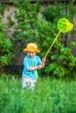 Het charmante jong geitje spelen met een lepel op een weide in een warme en zonnige de zomer of de lentedag stock foto