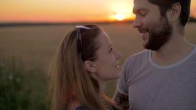 Het charmante jonge paar kussen op tarwegebied bij zonsondergang stock videobeelden