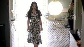 Het charmante jonge Spaanse meisjesmodel met zwart haar in een lange transparante kleding, gaat elegant door cafetariazaal over C stock video