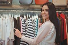Het charmante jonge vrouw winkelen bij kledingsopslag royalty-vrije stock afbeeldingen